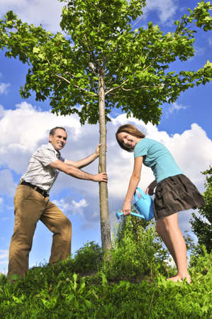 Father and daughter watering a young tree 스톡 콘텐츠