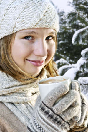 Teenage girl in winter hat with cup of hot chocolate 写真素材