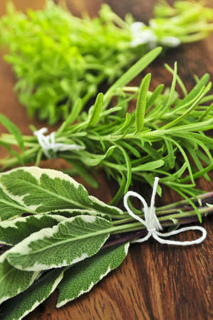 Bunches of assorted fresh herbs close up on wooden cutting board photo