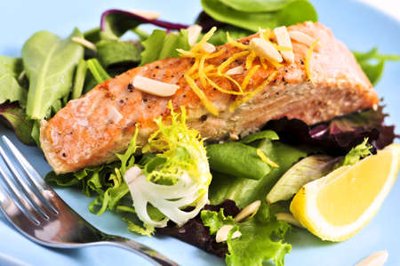 Green salad with grilled salmon fillet and lemon photo
