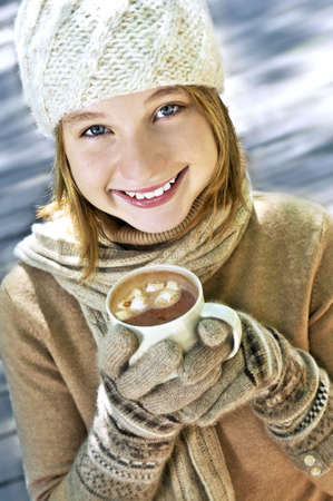 Teenage girl in winter hat with cup of hot chocolate photo