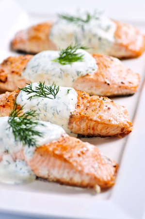 grilled salmon: Cooked salmon fillets with dill sauce on white plate Stock Photo