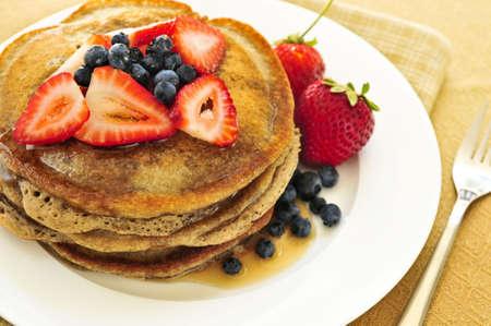 palatschinken: Stack von Buchweizen-Pfannkuchen mit frischen Beeren und Ahornsirup