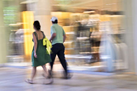fronts: Couple shopping in a mall, panning shot, intentional in-camera motion blur
