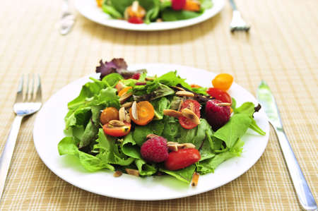 Healthy green salad with berries and cherry tomatoes photo