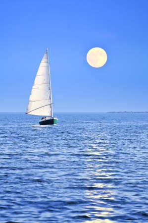 Sailboat sailing in a sea at full moon night photo
