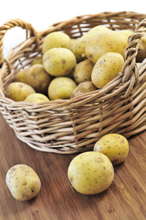 starchy food: Yellow raw potatoes in a basket close up Stock Photo