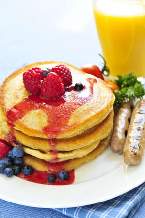 Breakfast of buttermilk pancakes with sausages and fresh berries Фото со стока