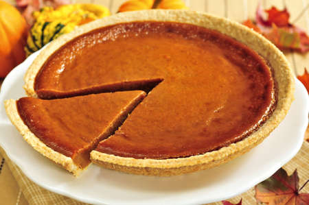 Whole pumpkin pie with a slice cut out 写真素材