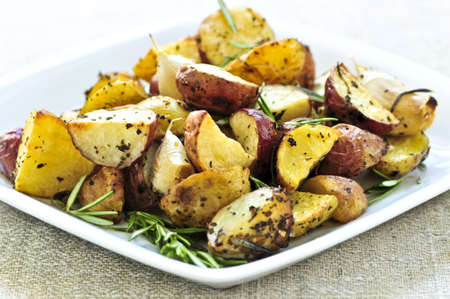 wedges: Herb roasted potatoes served on a plate Stock Photo