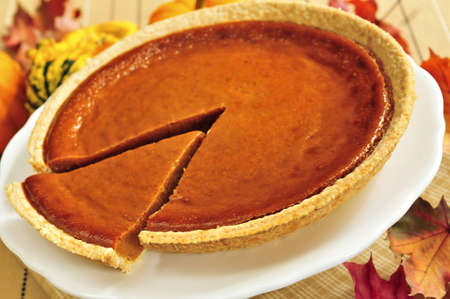 Whole pumpkin pie with a slice cut out Stock Photo