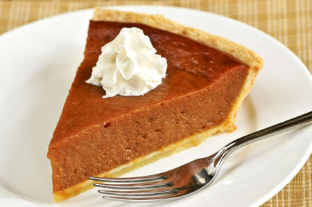 Slice of pumpkin pie with fresh whipped cream