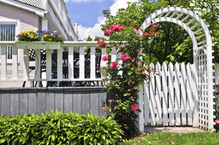 pergola: White arbor with red blooming roses in a garden