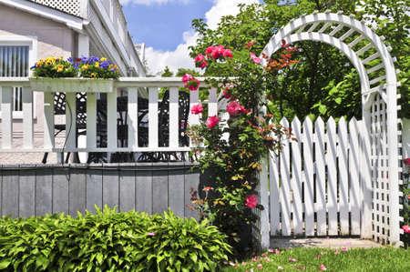 Witte prieel met rode bloeiende rozen in een tuin