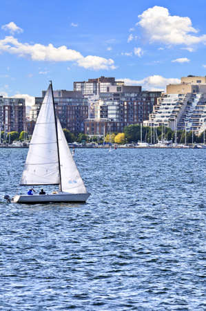 Sailboat sailing in Toronto harbour with scenic waterfront view photo