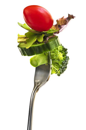 Fresh vegetables on a fork isolated on white background photo