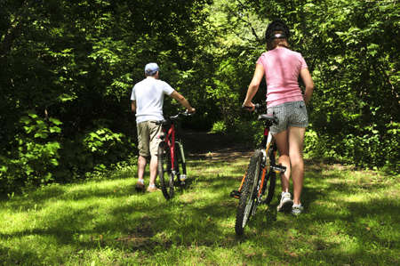 Teenage girl and her father with bicycles in summer park photo