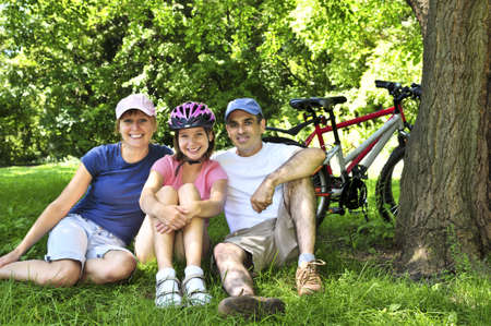 cycling   helmet: Family resting in summer park with bicycles Stock Photo