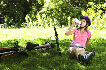 Teenage girl resting in a park with a bicycle drinking water photo