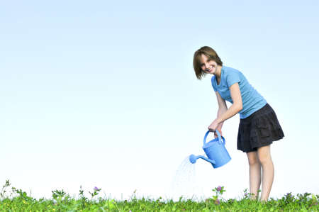 Smiling teenage girl with watering can on green grass photo
