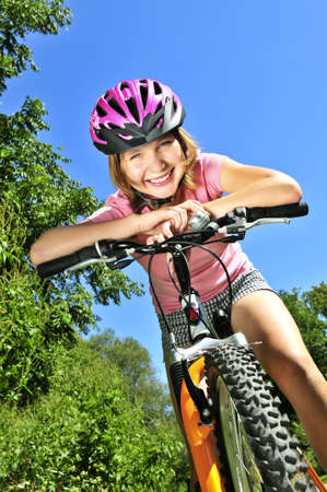 Portrait of a teenage girl on a bicycle in summer park outdoors photo
