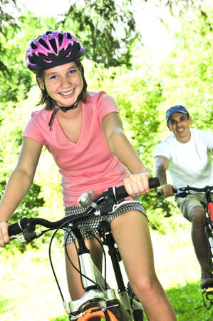 Teenage girl and her father riding bicycles in summer park photo