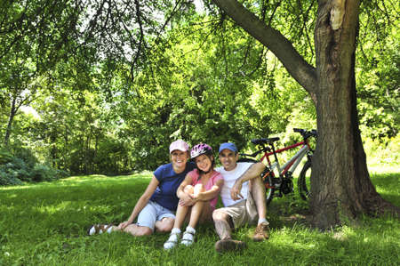Family resting in summer park with bicycles photo
