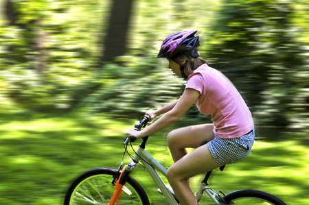 Portrait of a teenage girl riding a bicycle in summer park outdoors