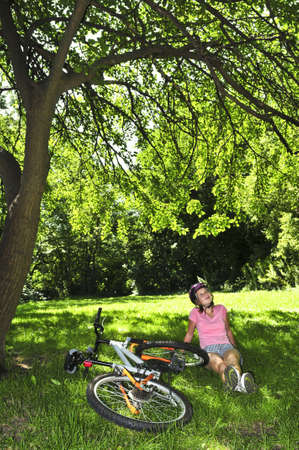 Teenage girl relaxing under green tree with her bicycle Stock Photo