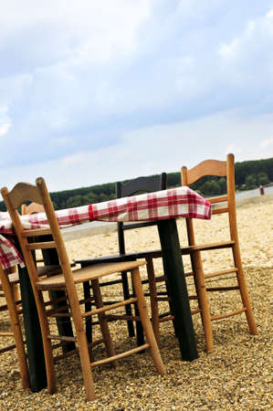 Dining table and chairs set outside on a beach photo
