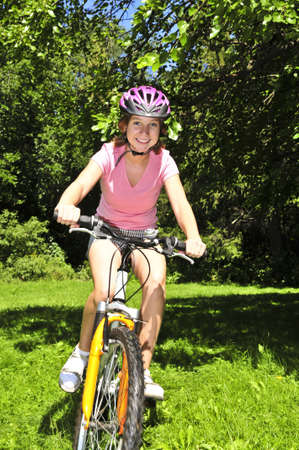 Portrait of a teenage girl riding a bicycle in summer park outdoors Stock Photo - 3903189