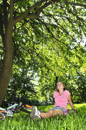 Teenage girl relaxing under green tree with her bicycle photo