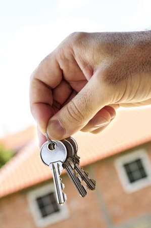 Mans hand holding keys with a house under construction in background photo