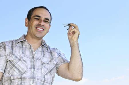 Smiling man holding house keys on blue sky background photo