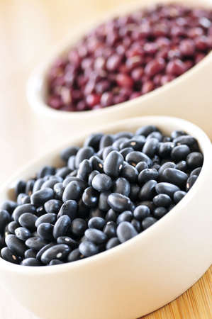 Dry black and red adzuki beans in bowls photo