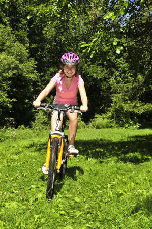 Portrait of a teenage girl riding a bicycle in summer park outdoors photo