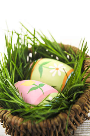 Easter eggs arrangement with green grass in a basket photo