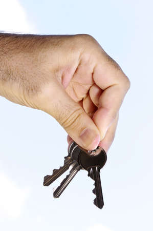 Man's hand holding house keys on blue sky background Stock Photo - 3931502