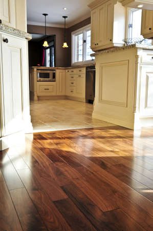 hardwood: Hardwood and tile floor in residential home kitchen and dining room