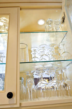 Kitchen cabinet close up with glass shelves and glasses photo