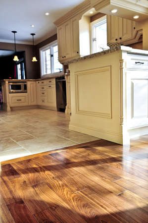wood flooring: Hardwood and tile floor in residential home kitchen and dining room