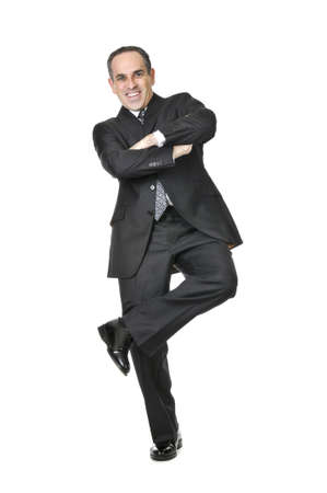 Happy businessman in a suit standing on one leg isolated on white background