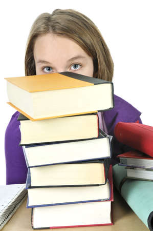Frustrated teenage girl studying at the desk with big stack of books