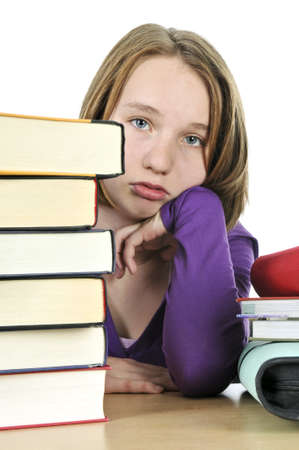 unmotivated: Frustrated teenage girl studying at the desk with big stack of books