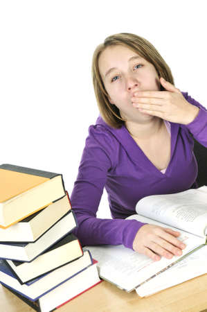 unmotivated: Yawning teenage girl studying at the desk