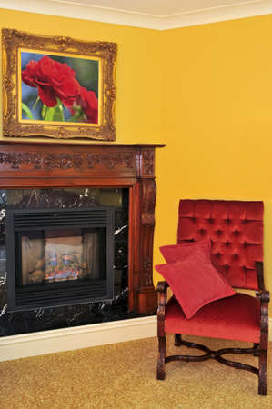 Fireplace and red chair, image on the wall is my own photo