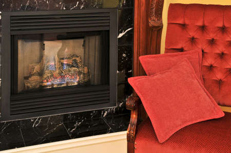 luxury hotel room: Fireplace and red chair in living room