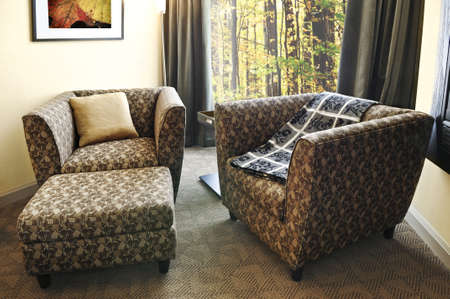 Comfortable armchairs with cushion and ottoman. Photo on the wall is my own. photo