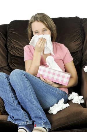 Teenage girl with a cold sitting in a chair with tissue box