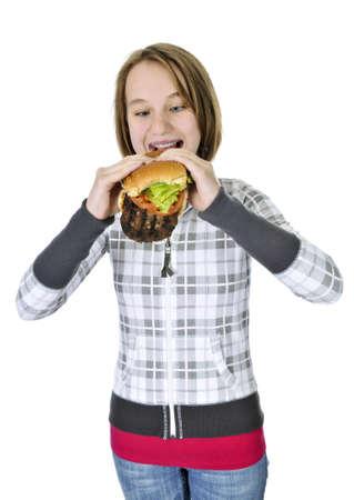 Teenage girl eating a big hamburger isolated on white background photo